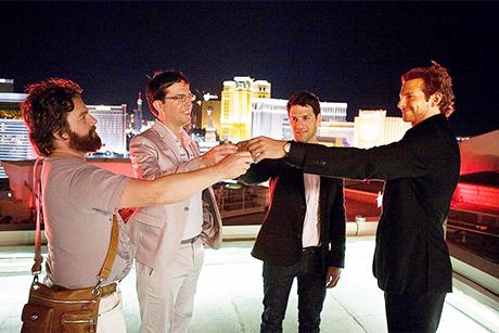 Os quatro amigos brindam no topo de um prédio
