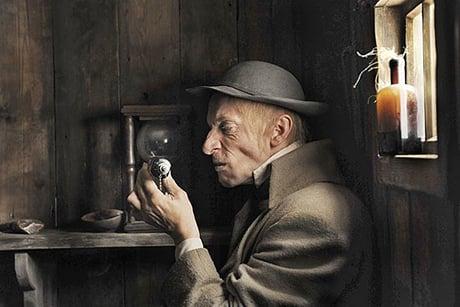 Homem de rosto enrugado observa objeto em cena que lembra um quadro