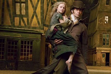 Hugh Jackman segura menina no colo, com casa ao fundo