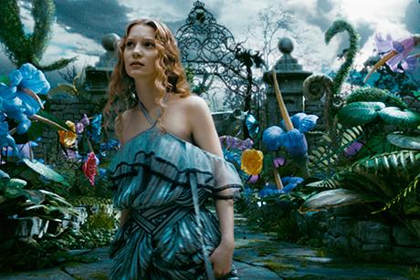 Mia Wasikowska com vestido largo, em cenário colorido de floresta