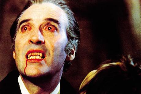 Christopher Lee com olhos vermelhos e sangue nos dentes