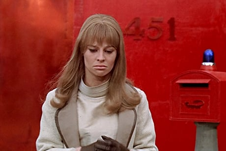 Julie Christie olha para baixo, sob fundo vermelho
