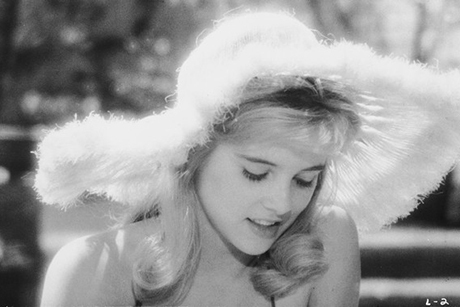 Shelley Winters sorri olhando para baixo, com chapéu felpudo. Preto e branco