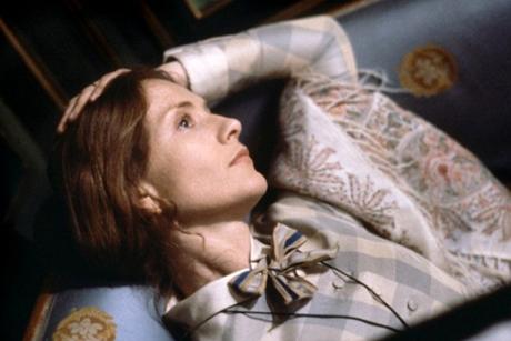 Isabelle Huppert deitada, com a mão na cabeça