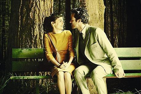 Audrey Tatou e Romain Duris sentados em banco em A Espuma dos Dias